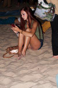 sexy am strand ohne slip mit handy in der hand 2